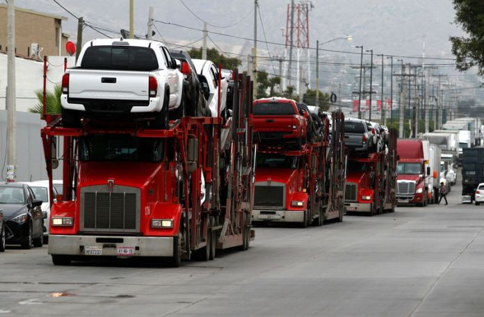 © -. A carrier trailer transports Toyota cars for delivery while queuing at the border customs control to cross into the U.S.