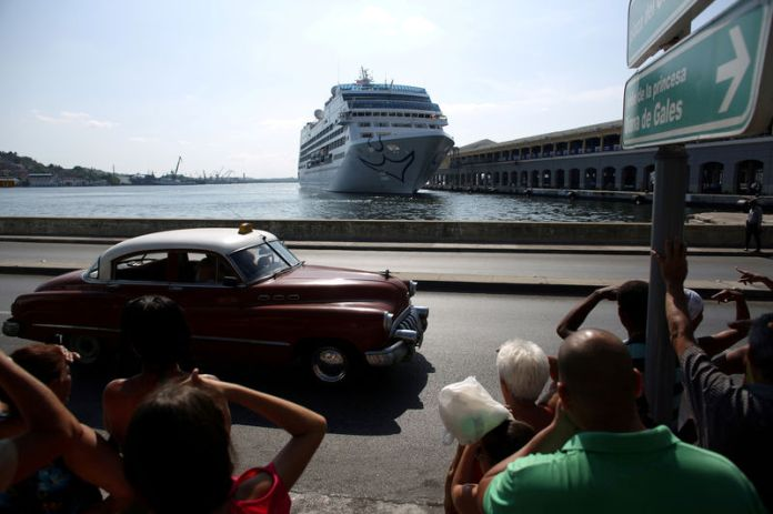 © -. FILE PHOTO: People look at the arrival of U.S. Carnival cruise ship Adonia at the Havana bay, the first cruise liner to sail between the United States and Cuba since Cuba's 1959 revolution