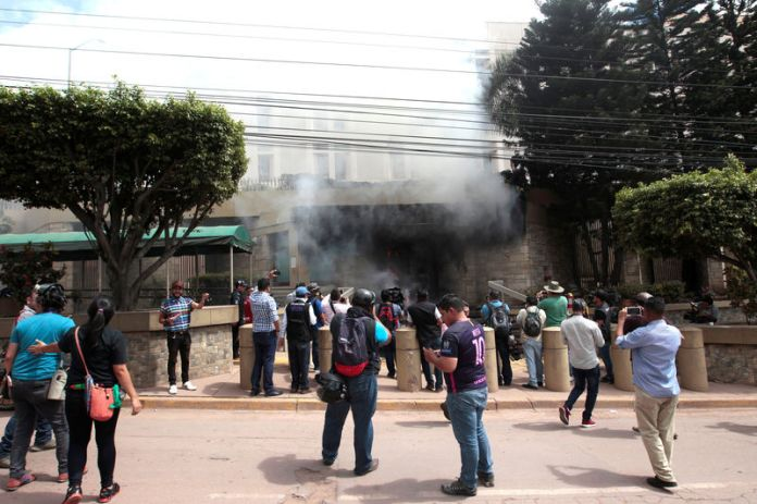 © -. Journalists are seen outside the U.S. Embassy after a demonstration against government privatisation plans in healthcare and education in Tegucigalpa