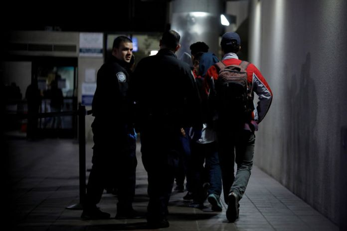 © -. FILE PHOTO: Unaccompanied minors, part of a caravan of thousands from Central America trying to reach the United States, are escorted by U.S. CBP officers as they have been processed for asylum at the Otay Mesa port of entry in San Diego