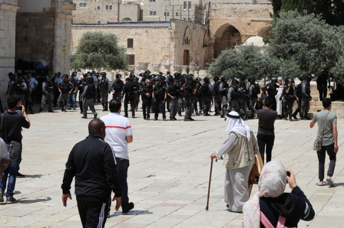 © -. Palestinians stand near Israeli policemen as clashes erupted with Palestinians on