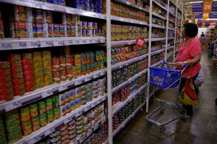 © -. Woman scans the selection of canned goods at a grocery store in Makati