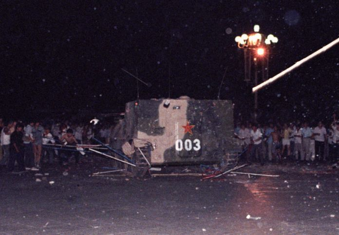 © -. FILE PHOTO: An armoured personnel carrier crushes one of the tents set up on Tiananmen Square by pro-democracy protesters early Sunday morning in Beijing