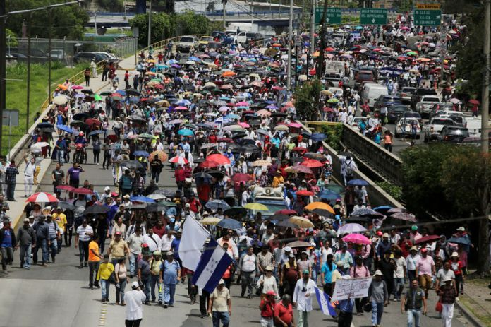 © -. Demonstrators march against President Juan Orlando Hernandez government's plans to privatize healthcare and education, in Tegucigalpa