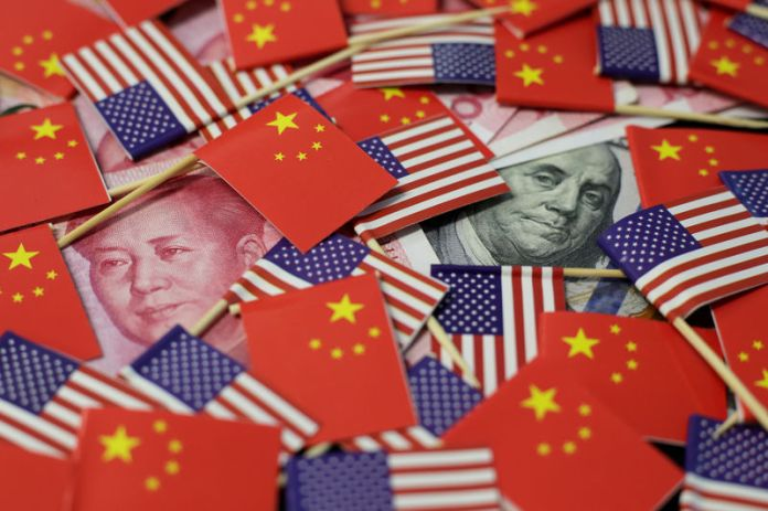 © -. Illustration picture showing U.S. dollar and China's yuan banknotes