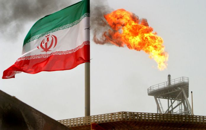 © Reuters. FILE PHOTO: A gas flare on an oil production platform in the Soroush oil fields is seen alongside an Iranian flag in the Persian Gulf