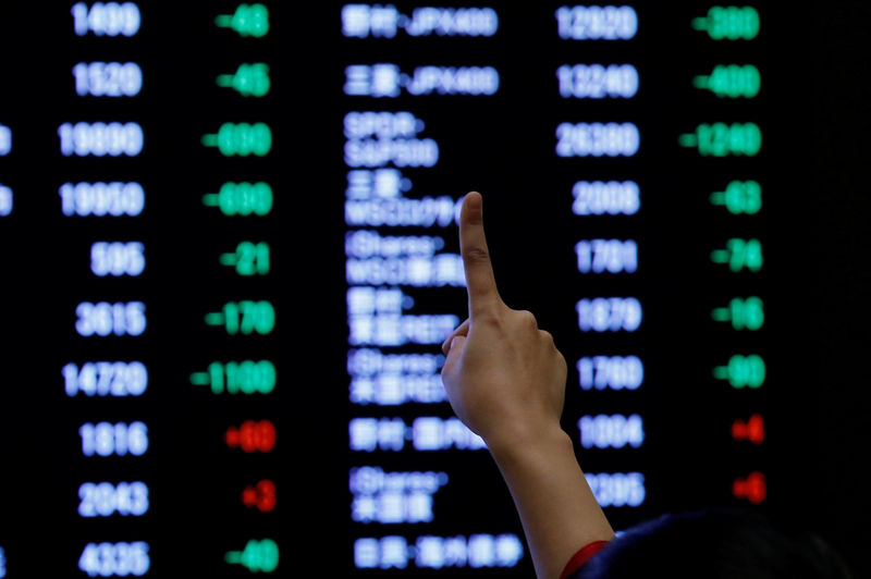 © Reuters. A woman points to an electronic board showing stock prices as she poses in front of the board after the New Year opening ceremony at the Tokyo Stock Exchange (TSE), held to wish for the success of Japan's stock market, in Tokyo