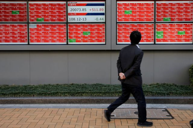 © Reuters. FILE PHOTO: A man looks at an electronic board showing the Nikkei stock index outside a brokerage in Tokyo