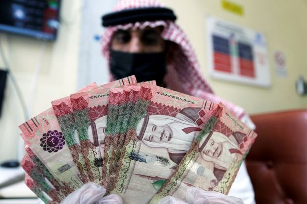 © Reuters. FILE PHOTO: A Saudi money exchanger wears a protective face mask and gloves, as he counts Saudi riyal currency at a currency exchange shop in Riyadh