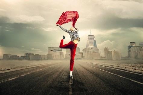 Mujer feliz saltando vestida de rojo.