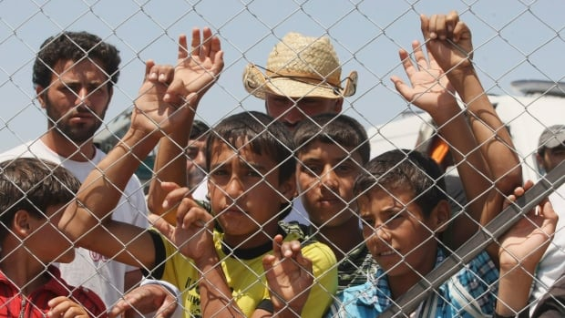 Refugee children look out from a fence from inside a Syrian refugee camp just at the border in Turkey in June 2011.  The UN's health agency said Tuesday it has confirmed 10 polio cases in northeast Syria, the first confirmed outbreak of the diseases in Syria in 14 years.