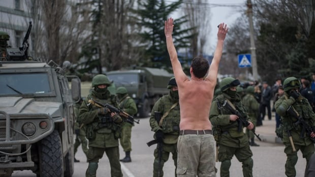 A Ukrainian man stands in protest in front of gunmen in unmarked uniforms as they stand guard in Ukraine. Russian President Vladimir Putin wrested control of the Ukrainian Black Sea region of Crimea from Kyiv on Saturday, citing a threat to Russian citizens and servicemen based there.