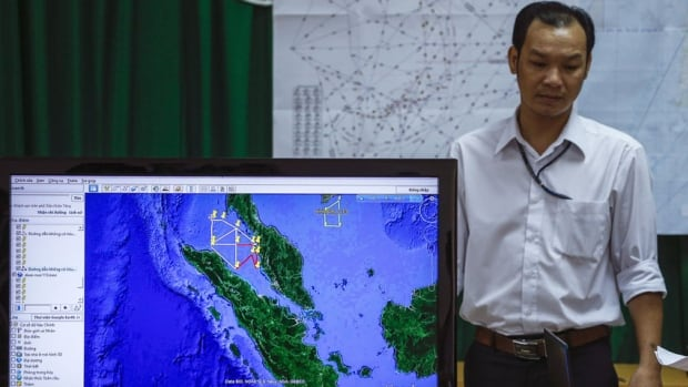 A Vietnamese officer stands beside a TV screen showing missing Malaysia Airlines flight MH370's flight path. On Wednesday, Chinese state media reported that a Chinese satellite spotted possible debris from the jet, with images available on a Chinese government website.