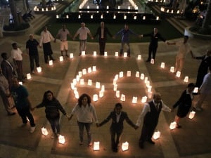Employees of the Jumeirah Messilah Beach Hotel surround candles during Earth Hour on March 29, 2014, in Kuwait. Lights go off around the world at 8.30pm local time for the annual event meant to raise awareness about climate change and the environment.