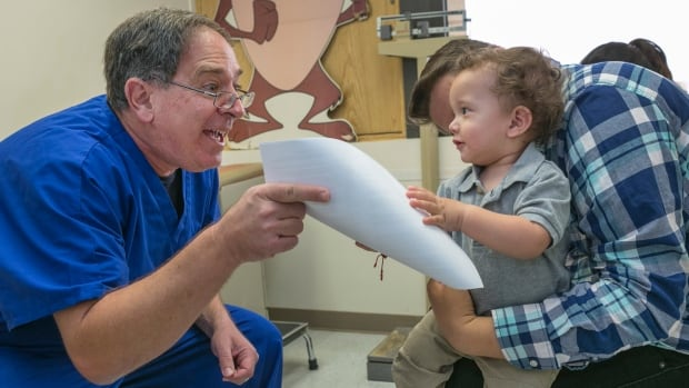 Pediatrician Charles Goodman, left, explains to Frank Fierro, the father of 1 year-old Cameron Fierro, the need to get the measles-mumps-rubella vaccine.