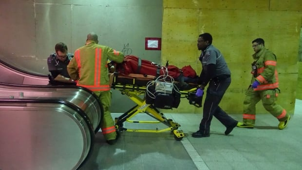 Ambulance technicians remove an injured 18-year-old man after he was stabbed at the Rosemont metro station.