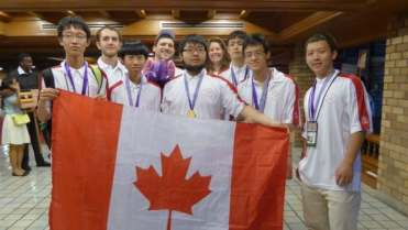 Left to right: Jinhao (Hunter) Xu, James Rickards (Observer), Kevin Sun, Jacob Tsimerman (Leader), Zhuo Qun (Alex) Song, Lindsey Shorser (Deputy Leader), Alexander Whatley, Michael Pang, Yan (Bill) Huang are shown at the International Mathematical Olympiad in Thailand on July 16, 2015.
