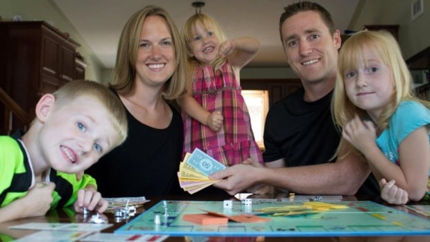 Mandy Knight, 34, with husband, Derek, 33, and their children, Ethan, 5, Evelyn, 3, and Madelyn, 7, playing Monopoly in their Port Dover, Ont home. The Knights are super savers which means they're flush with cash — even during the tough times.
