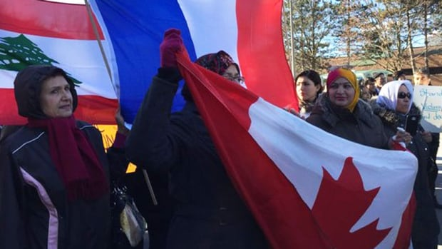 Marchers carried the Canadian, French and Lebanese flags during a Friday peace march in the Flemingdon Park neighbourhood.
