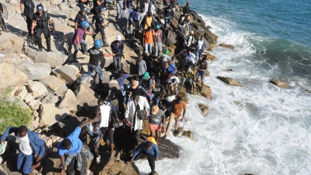 Migrants on a seawall try to get past a police cordon in Ventimiglia, an Italian town on the border with France, last week. Italian and French police reportedly fired tear gas trying to prevent the migrants from swimming and walking across the border to France.