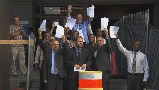 Members of a group that represents taxi drivers hold up copies of the injunction, filed on Thursday. (CBC)