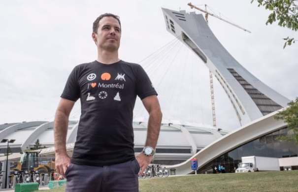 Pier-Luk Bouthillier wearing his t-shirt in front of the Montreal Olympic stadium. (Photo: Paul Chiasson/The Canadian Press). So far, there have been no reports that SODRAC demands payment for the reproduction of the stadium in this image.