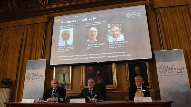 Nobel committee members announce the latest award at the Royal Swedish Academy of Sciences in Stockholm on Tuesday. David Thouless, Duncan Haldane and Michael Kosterlitz, left to right on the screen, share the 2016 Nobel Prize in Physics.