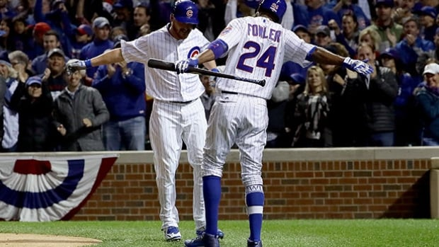 Cubs reliever Travis Wood, left, celebrates his home run with teammate Dexter Fowler (24) on Saturday night in Chicago. The Cubs defeated the Giants to take a 2-0 lead in their NLDS matchup. (Jonathan Daniel/Getty Images)