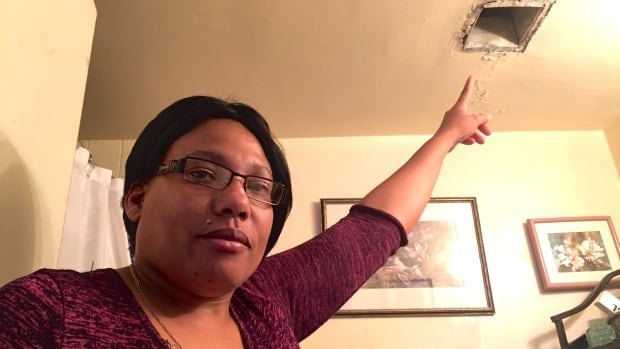 Cheryl Horne points out a hole in the bathroom of her Scarborough apartment that has gone unfixed for five years.