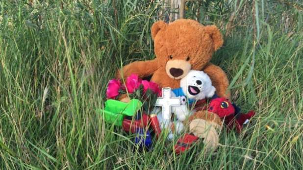 Teddy bears are placed near the pond where the young boy was found Monday morning.