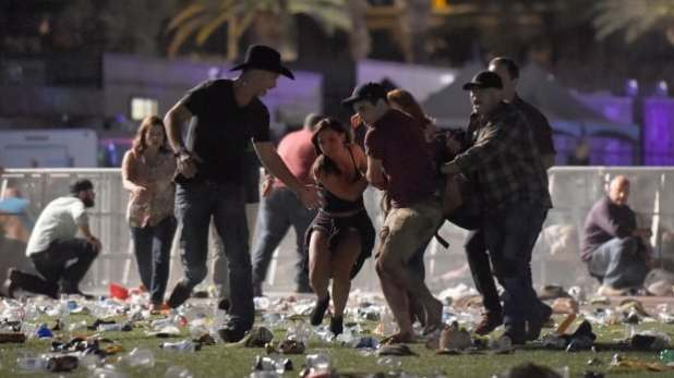 People carry a person at the Route 91 Harvest country music festival after apparent gun fire was heard on October 1 in Las Vegas.