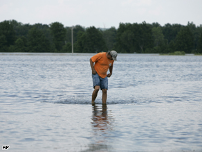 Mark Rowland wades through floodwater near his home, June 19. Levels have risen in Lincoln County since then.