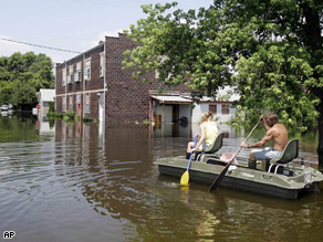 Frankie Davis and her husband paddle a boat through floodwaters back to their house in Foley, Mo., Wenesday.