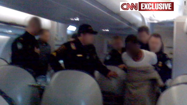 CNN obtained this exclusive photo of the suspect being taken into custody on board the plane.