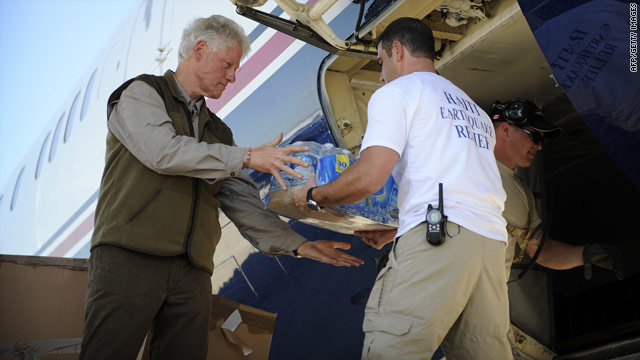 Bill Clinton takes bottles of water out of his plane January 18 at the international airport for Port-au-Prince, Haiti.
