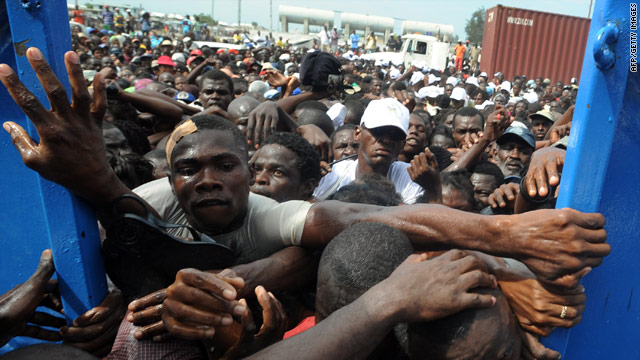 Haitians desperately try to enter the police station where an aid distribution point has been set up in Port-au-Prince.