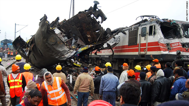A damaged coach is moved from the wreckage Saturday after a deadly collision near Kanpur, India.