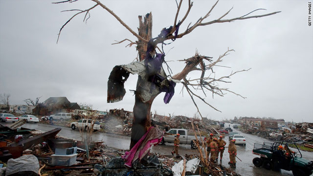 A rescue team searches house to house for survivors Monday after a deadly tornado struck Joplin, Missouri.