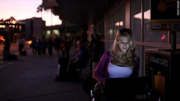 Nicole Kinsler of Denver checks for hotels online outside San Diego International Airport after a power outage hit California.