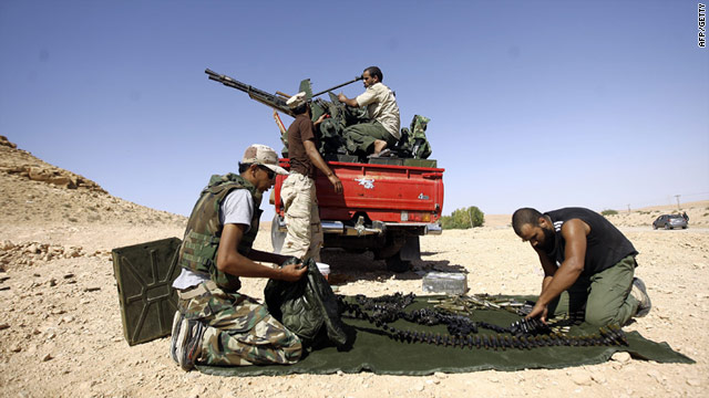 Libyan fighters loyal to the NTC load ammunition along the frontline with the town of Bani Walid on September 11, 2011.