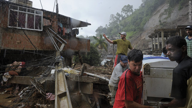 People salvage a refrigerator from a house destroyed by a mudslide Saturday in Nova Friburgo, Brazil.
