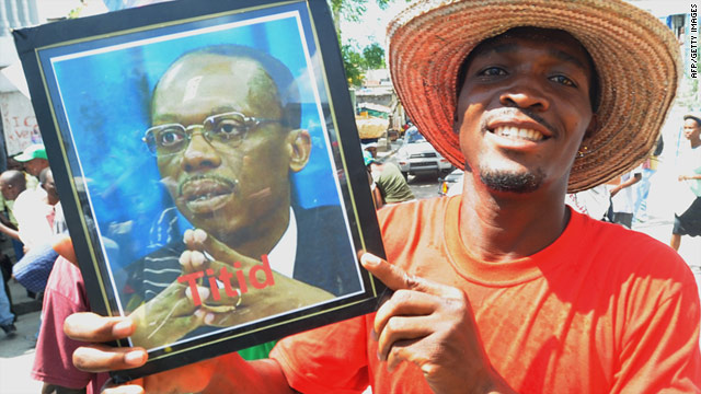 A supporter of former Haitian President Jean-Bertrand Aristide holds a sign last month at a rally calling for Aristide's return.