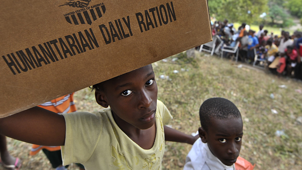 A Haitian child carries food at a refugee camp in Port-au-Prince. (Getty Images)
