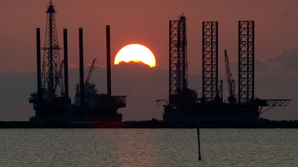 E. M. PIO RODA/CNN  The sun sets behind two offshore oil platform rigs under construction Monday, June 15 in Port Fourchon, Louisiana. - CNN