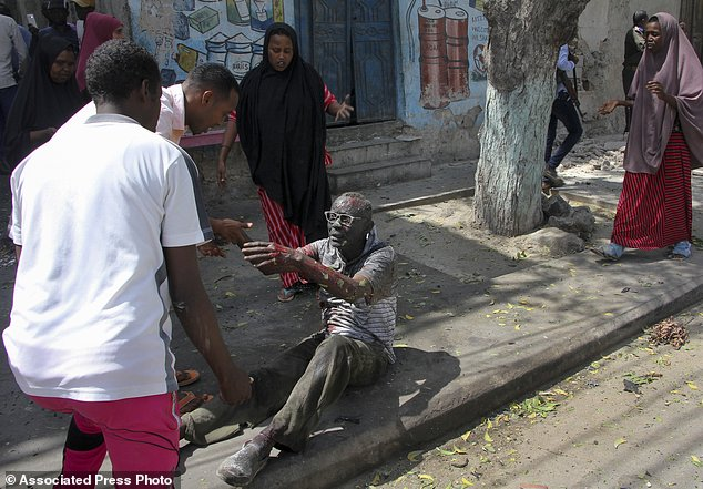 A wounded man reaches out to rescuers after a car bomb attack in Mogadishu, Somalia Monday, March 13, 2017. A suicide car bomber detonated near the Weheliye hotel in the capital Monday morning, killing a number of people on the busy Maka Almukarramah road, police said. (AP Photo/Farah Abdi Warsameh)