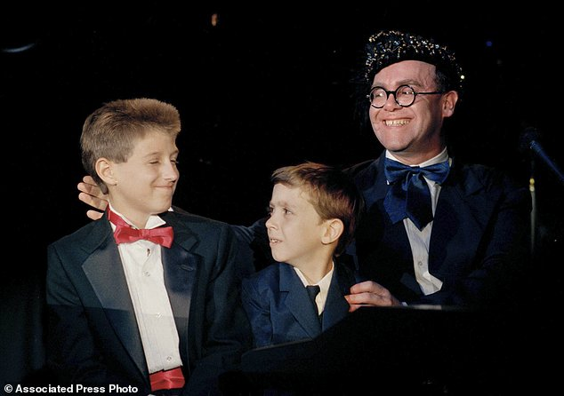 """FILE - In this July 9, 1988 file photo, AIDS activists, Ryan White, left, Jason Robertson, center, and British pop singer Elton John appear together at """"For the Love of Children"""" benefit for children with AIDS and other serious illnesses in Los Angeles. The Children's Museum of Indianapolis is planning a public exhibit displaying thousands of letters that people sent to Ryan White, a Kokomo, Ind., teenager who died of AIDS nearly 27 years ago. (AP Photo/Alan Greth, File)"""