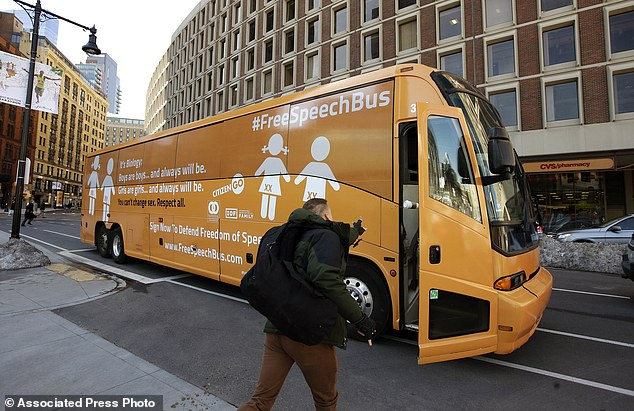 A protester throws a coffee cup at the 'Free Speech Bus' outside the City Hall in Boston
