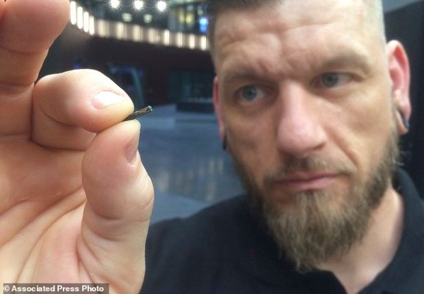Self-described 'body hacker' Jowan Osterlund from Biohax Sweden, holds a small microchip implant, similar to those implanted into workers at the Epicenter digital innovation business centre during a party at the co-working space in central Stockholm