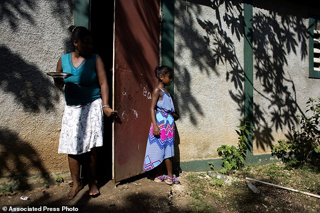 Marie-Ange Haitis, 40, stands with her daughter, Samantha, at their home in Leogane, Haiti