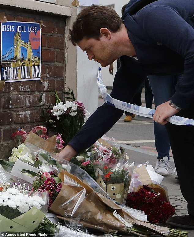 A man lays flowers at a corner tribute in the London Bridge area of London, Sunday, June 4, 2017. Police specialists collected evidence in the heart of London after a series of attacks described as terrorism killed several people and injured more than 40 others. (AP Photo/Frank Augstein)